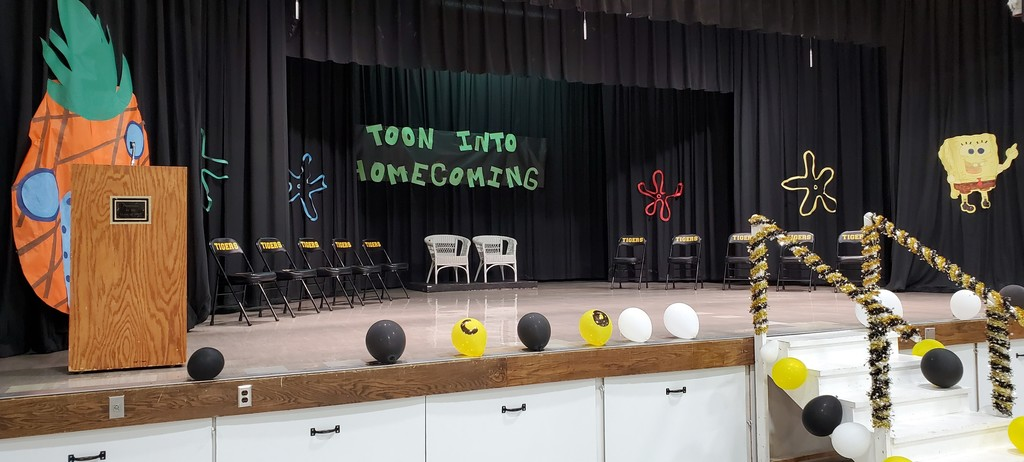 "Chairs on the stage with sign ""Toon Into Homecoming"""