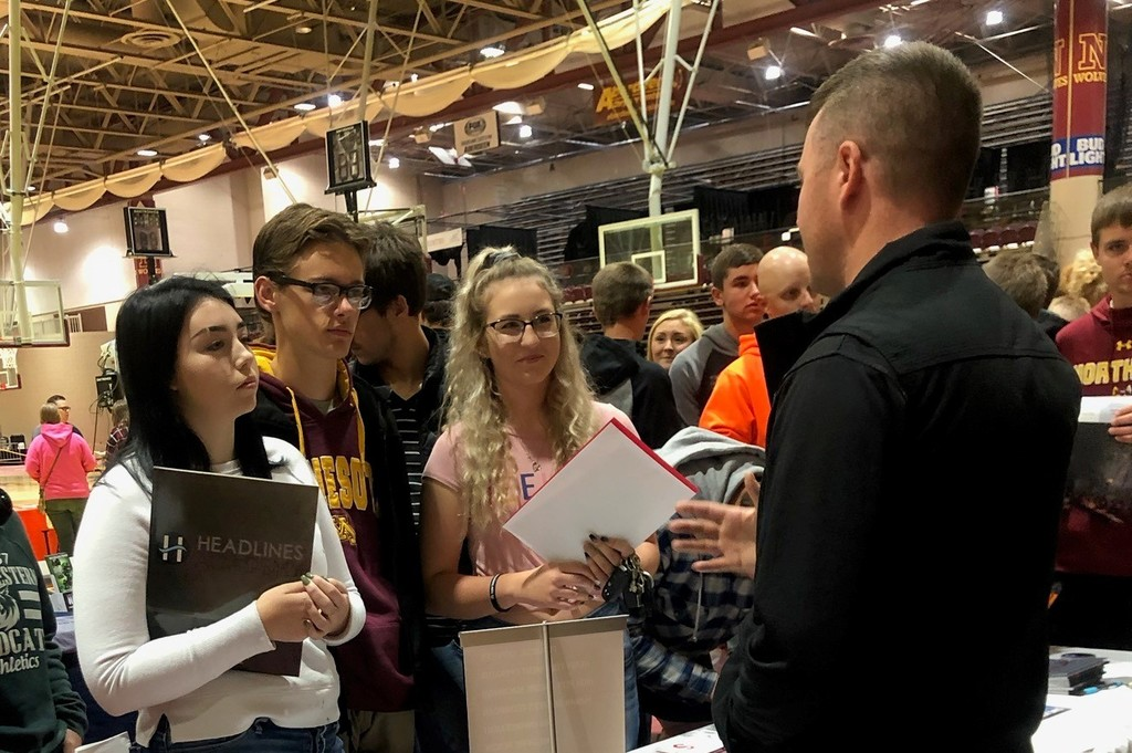 Students talking with college admission representatives.